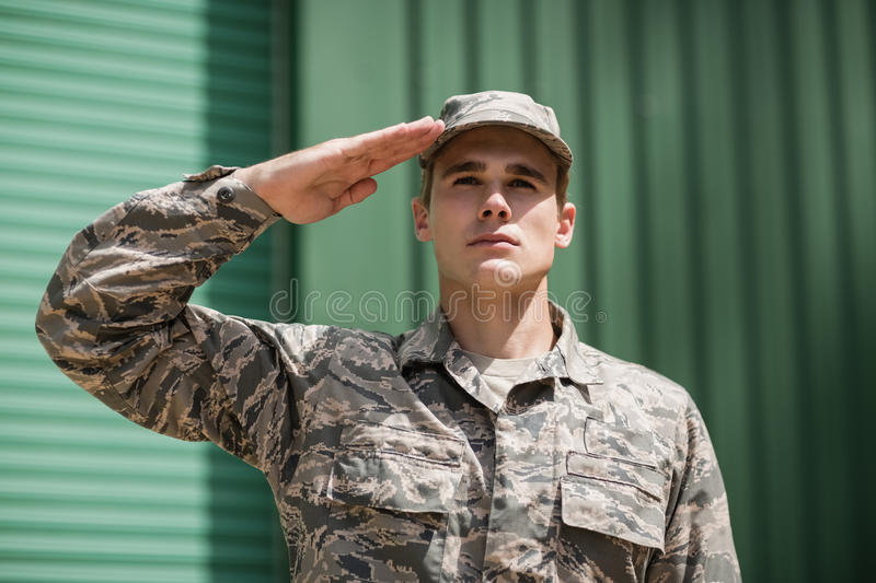 Close-up of military soldier giving salute. In boot camp stock photography