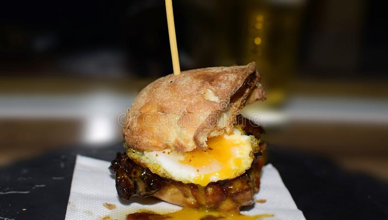 Close up mini burger with grilled angus beef, bacon, cheese,fried quail eggs, and cream sauces on thecraft paper and wooden stock image