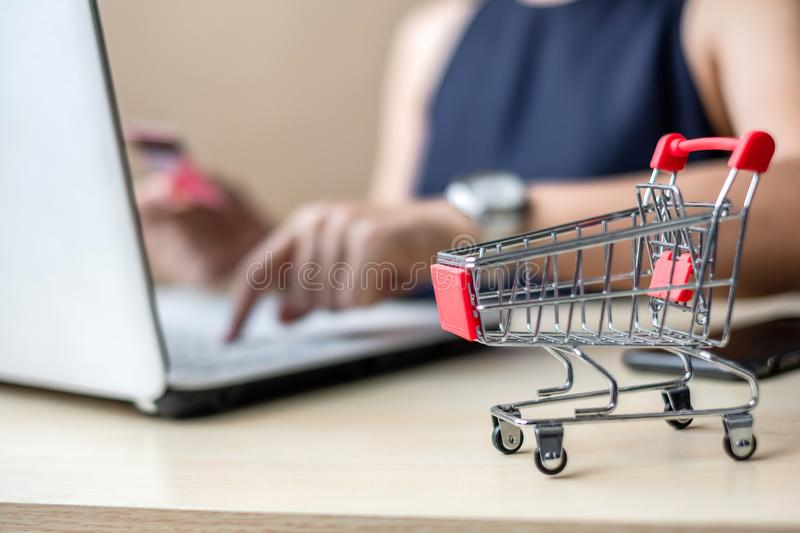 Close up mini cart, Asian businesswoman holding credit card and using laptop for online shopping while making orders. internet, royalty free stock photo
