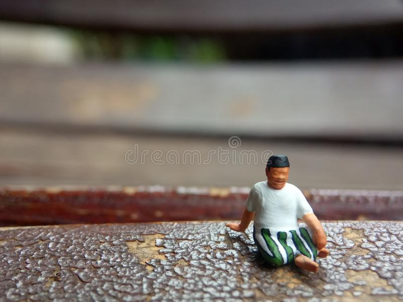 Mini figure toy old man sit at scratch wooden chair, with copy or negative space for text placement area stock photo