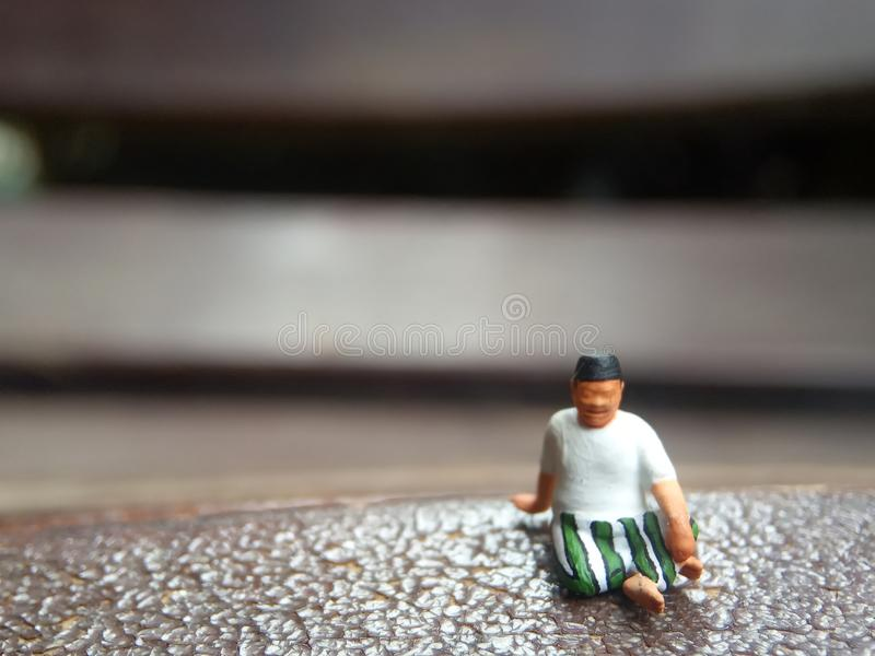 Mini figure toy old man sit at scratch wooden chair, with copy or negative space for text placement area royalty free stock photography