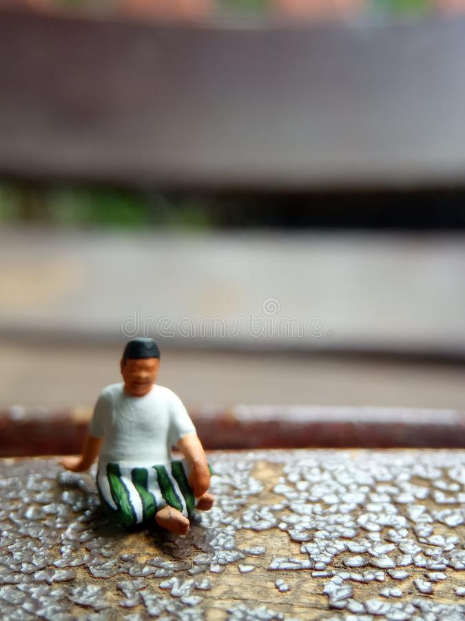 Mini figure toy old man sit at scratch wooden chair, with copy or negative space for text placement area royalty free stock photo