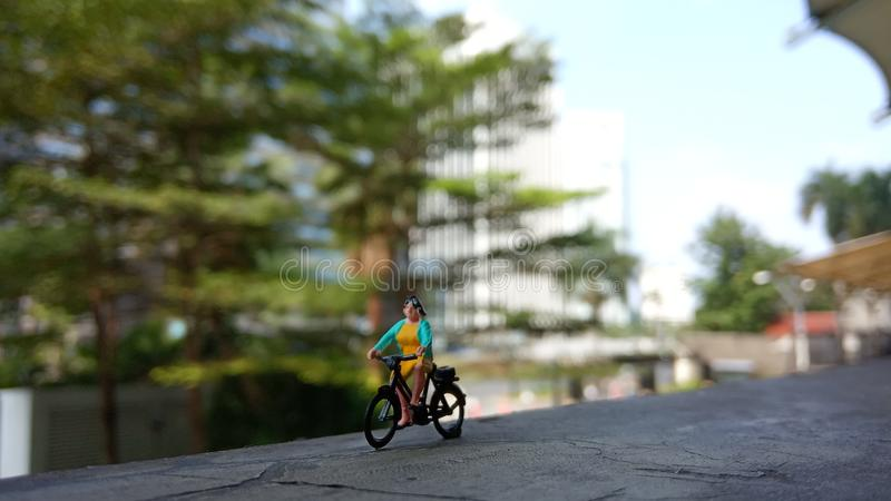 Close up Mini Figure Woman toys bicycling at Building Gate with negative or copy space for text area placement royalty free stock photo