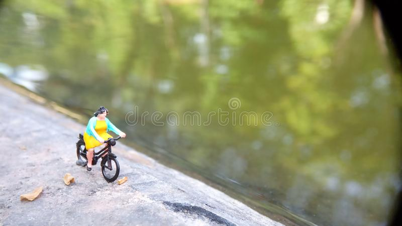 Close up Mini Figure Woman toys bicycling at River Side Path Way with negative or copy space for text area placement stock photo