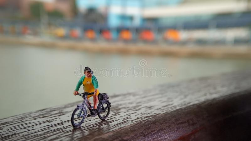 Close up Mini Figure Woman toys bicycling at River Side Path Way with negative or copy space for text area placement stock photography