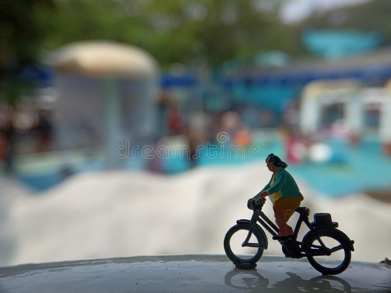 Close up Mini Figure Woman toys bicycling at Water Park White Horizontal Pool with negative or copy space for text area placement royalty free stock images