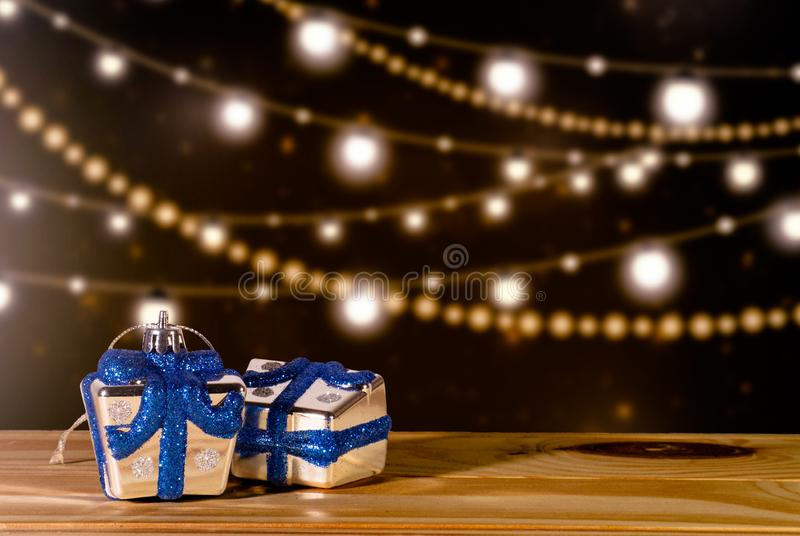 Close-up miniature gift boxes horizontal side view on table and light bulbs for decoration background. royalty free stock photos
