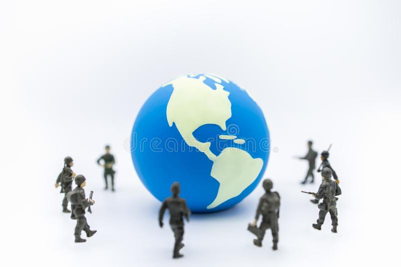 Close up of mini world ball with group of soldier miniature figure standing around royalty free stock photography