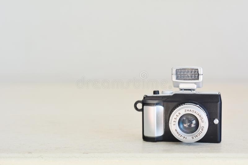 Close up of miniature toy retro camera on wood table. royalty free stock photography