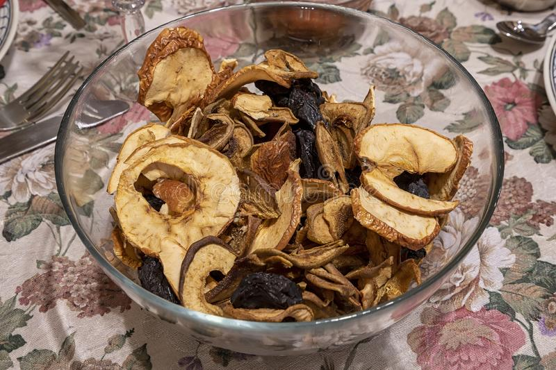 Close up of mixed dried fruit, prunes and sliced apples at the bowl on the table. royalty free stock photo