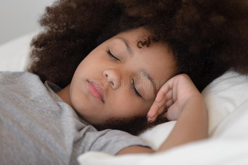 Close up mixed race cute peaceful child girl napping. stock photo