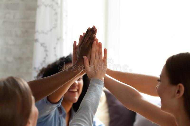 Close up diverse people giving high five. stock photos
