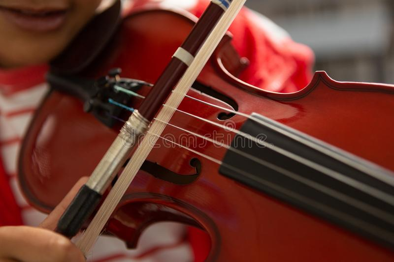 Schoolboy playing violin in classroom stock images