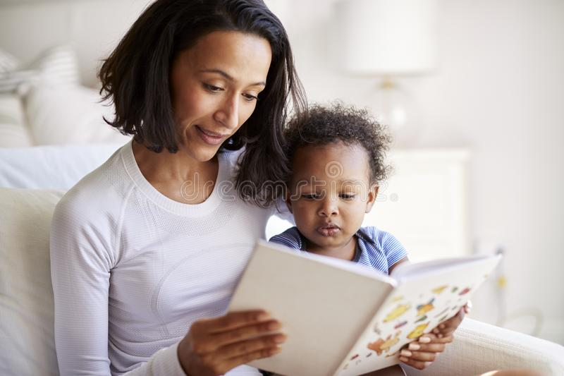 Close up of African American  young adult mother sitting in an armchair reading a book with her two year old son, close up royalty free stock photography