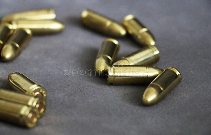Close up of 9 mm golden pistol bullets ammo on background. Special force units stock photo