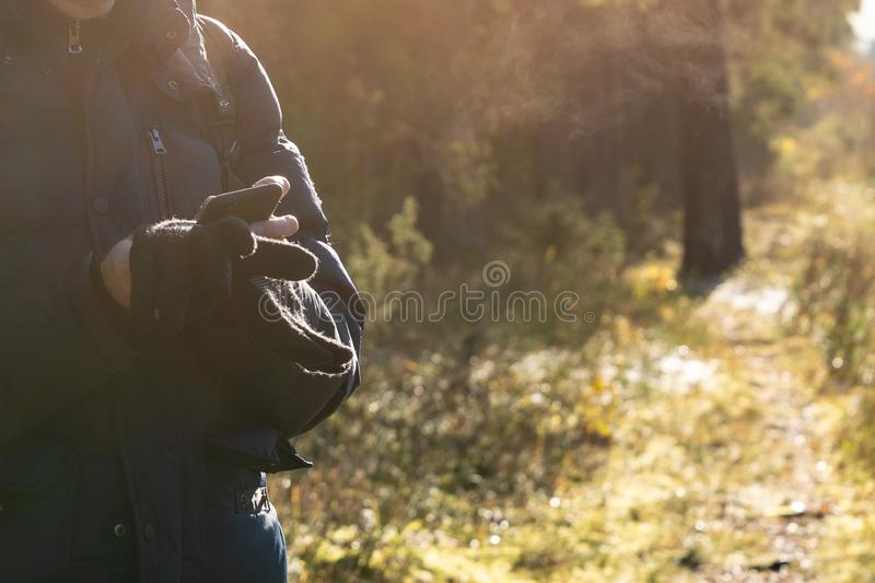 Close up of a man holding smart phone and standing on forest path royalty free stock image