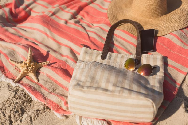 Close-up of mobile phone and accessories on picnic blanket at beach stock photography
