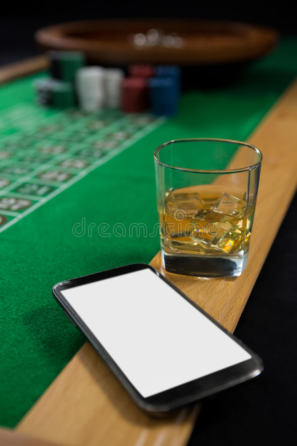 Close-up of mobile phone and whisky glass on roulette table royalty free stock photography