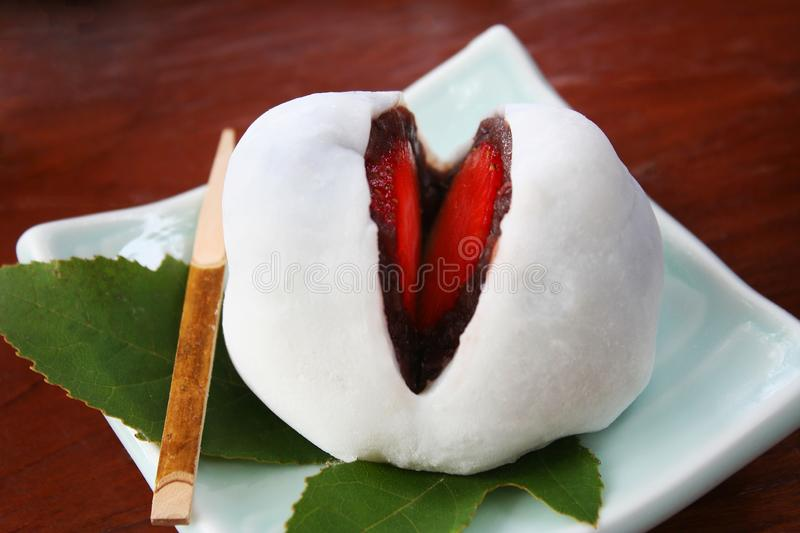Close up mochi candy dessert with slices of strawberry and sweet mashed taro on wooden background royalty free stock image