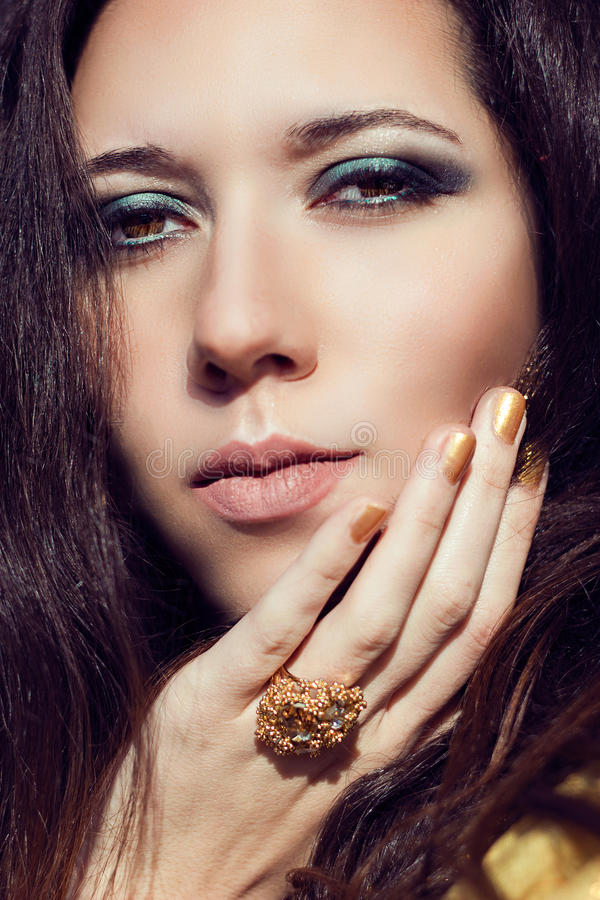 Close up model fashion portrait. Color smoky eyes turquoise. Close up fashion portrait of young beautiful woman brunette with long hair. Makeup color smoky eyes royalty free stock photo