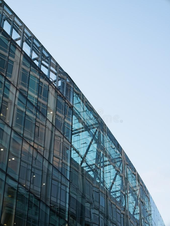 Close-up of modern corporate building with large glass windows against blue sky stock photo