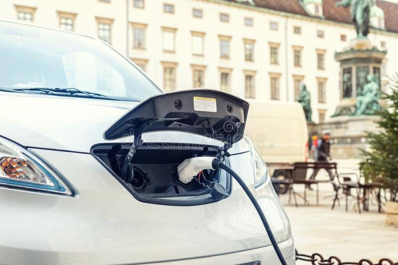 Close-up modern electric car pugged with fast charger at charging station in center of old European city. Ecol friendly green stock image