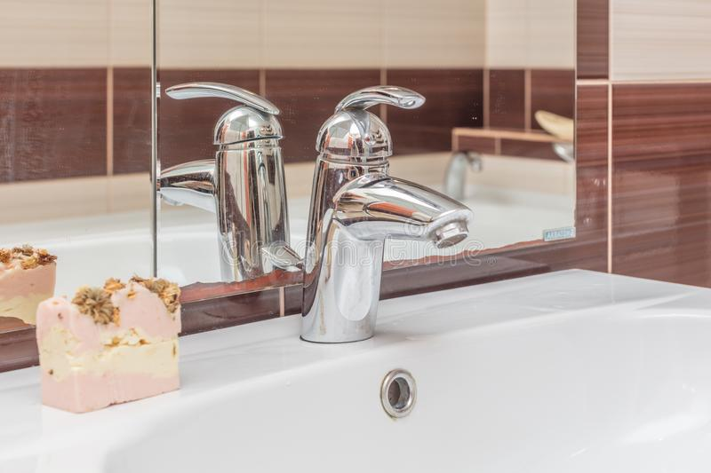 Faucet in bathroom. Close up of modern faucet and ceramic sink in bathroom stock image