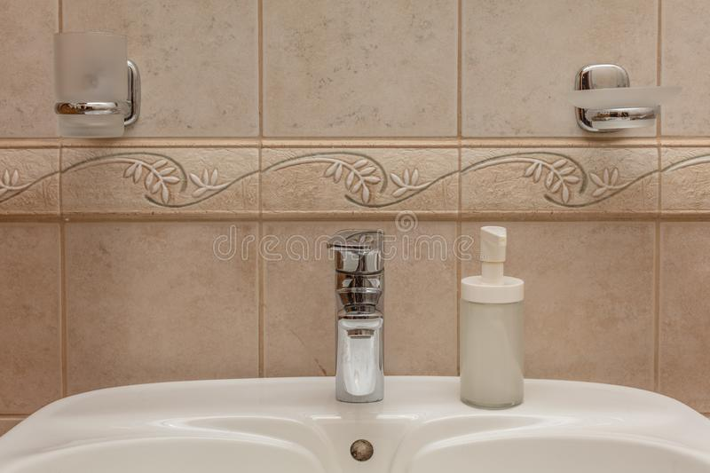 Faucet in bathroom. Close up of modern faucet and ceramic sink in bathroom stock images
