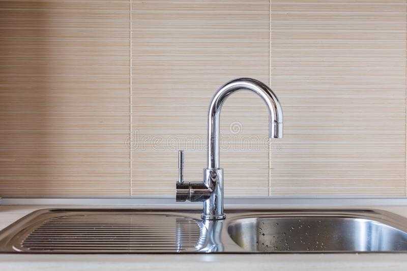 Faucet in kitchen. Close up of modern faucet and ceramic sink in kitchen royalty free stock image