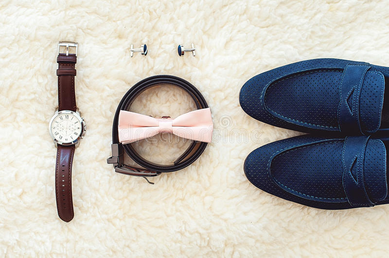 Close up of modern man accessories. Biege bowtie, leather shoes, belt, watch, cufflinks, money and wedding rings. Close up of modern man accessories. Biege royalty free stock image