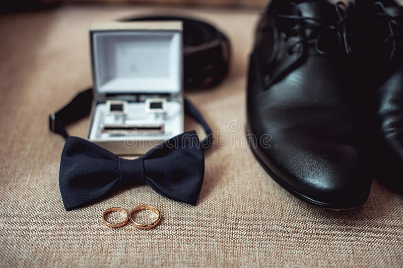 Close up of modern man accessories. wedding rings, black bowtie, leather shoes, belt and cufflinks stock photos