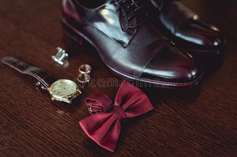 Close up of modern man accessories. wedding rings, cherry bowtie, leather shoes, watch and cufflinks royalty free stock image
