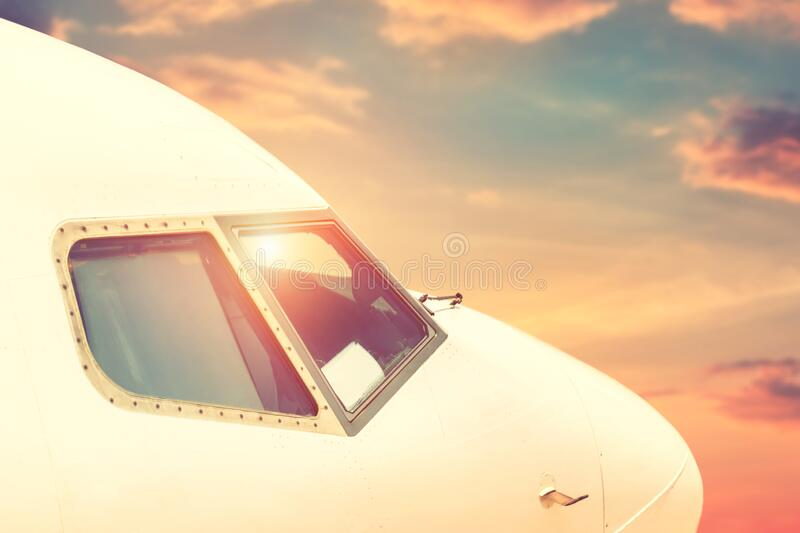 Close-up modern passenger commercial airplane cockpit flying against colorful dramatic sunset sky. Detail side view of royalty free stock image