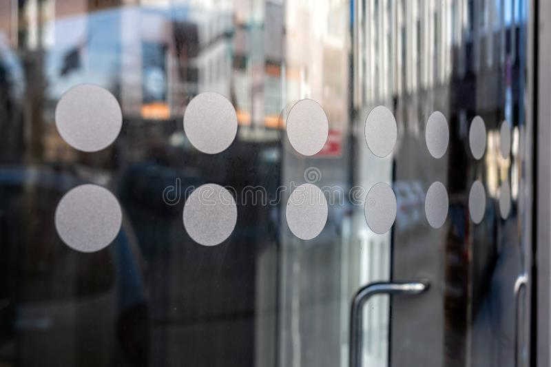 Close-up of modern secured glass door fragment at corporate business building. - Image stock photography