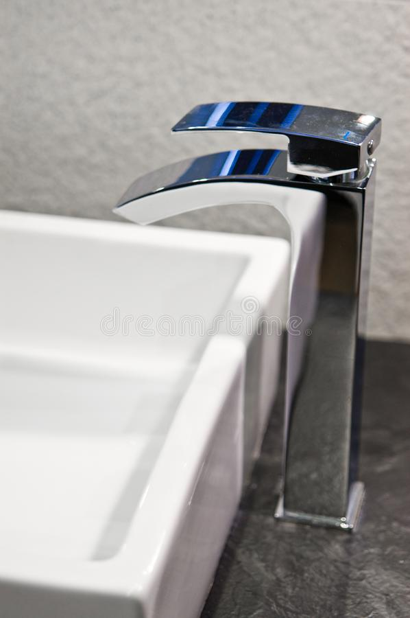Modern bathroom sink detail with chrome faucet. royalty free stock photo