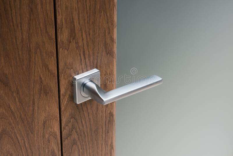Close-up of modern steel door handle on interior door. Dark oak and frosted glass royalty free stock image