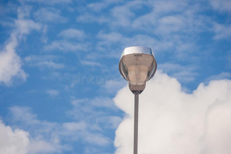 Modern stree lamp located on concrete floor beside road with blue sky background. royalty free stock images
