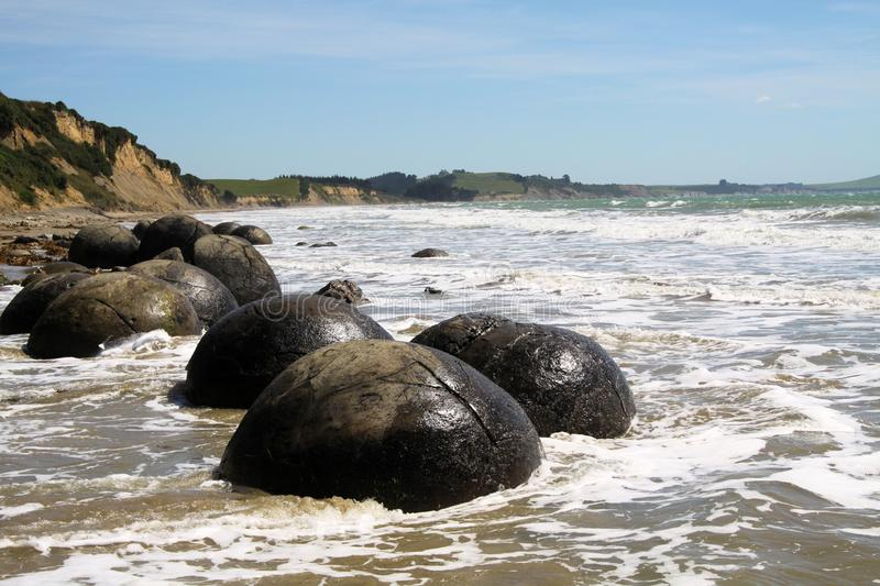 Close up of Moeraki spherical boulders of mudstone on the beach washed by surf of the sea, Koekohe Beach, Pebble beach New Zealand royalty free stock photos