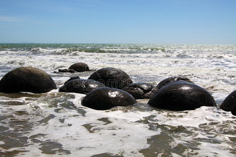 Close up of Moeraki spherical boulders of mudstone on the beach washed by surf of the sea, Koekohe Beach, Pebble beach New Zealand royalty free stock photography