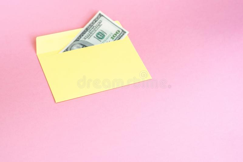 Close up of money in yellow envelope are lying on the pastel pink background.  Branding mock up; front view. On pink background royalty free stock image