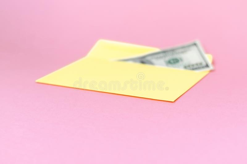Close up of money in yellow envelope are lying on the pastel pink background.  Branding mock up; front view. On pink background royalty free stock photos