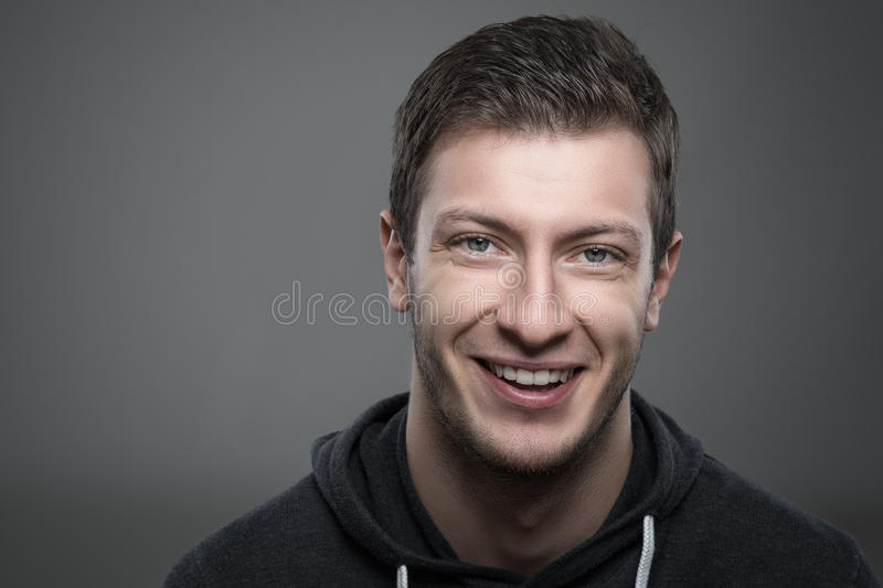 Close up moody portrait of young unshaven man smiling and looking at camera royalty free stock images