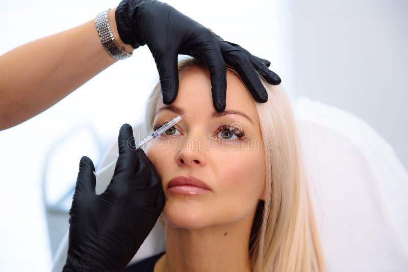 Close-up mooie vrouwelijke gezicht en cosmetologist` s handen met spuit tijdens gezichtsschoonheidsinjecties Verjonging en royalty-vrije stock afbeelding