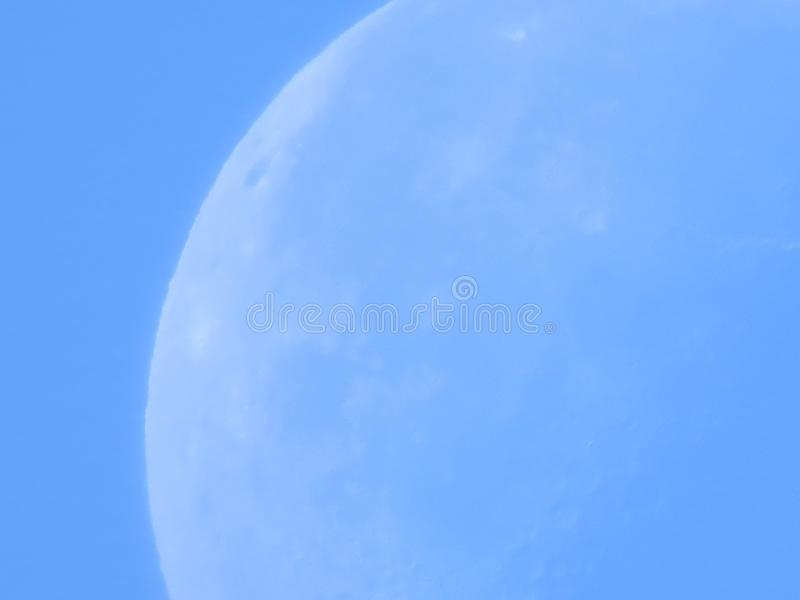 Close up of moon in a blue daylight sky. Close up of moon in a blue daylight sky showing details of the lunar surface royalty free stock photo