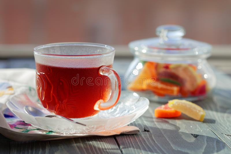 Close up of a morning black tea and colorful marmalades in glass jar on wooden table stock image