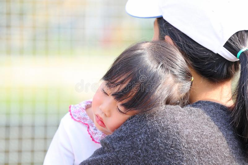 Close up mother carries child girl in her arms royalty free stock images
