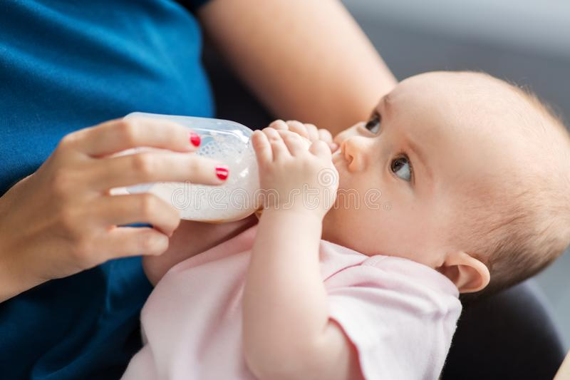 Close up of mother feeding baby with milk formula stock photo