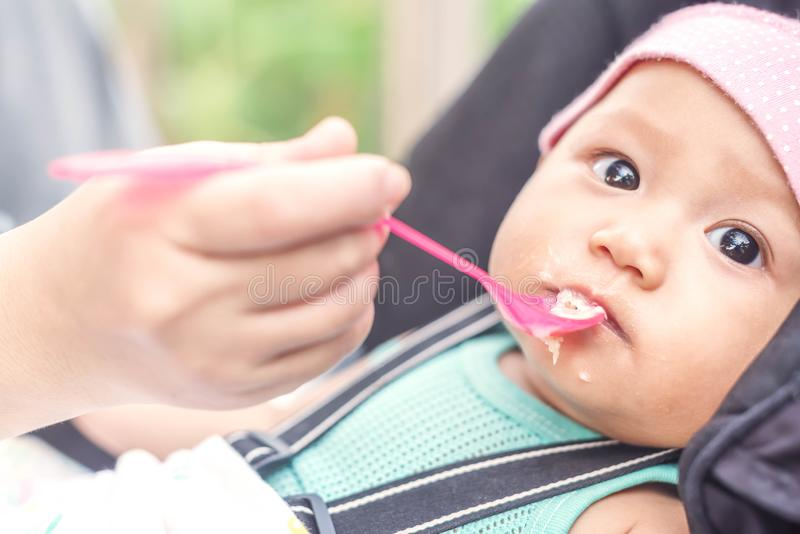 Close up mother hand, a sppon of baby food feeding her little cute baby girl for dinner stock image