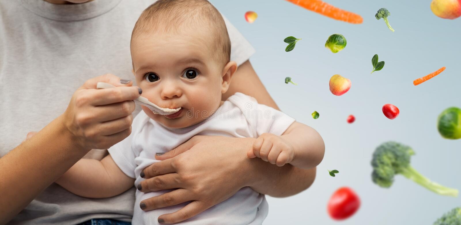 Close up of mother with spoon feeding little baby stock photography