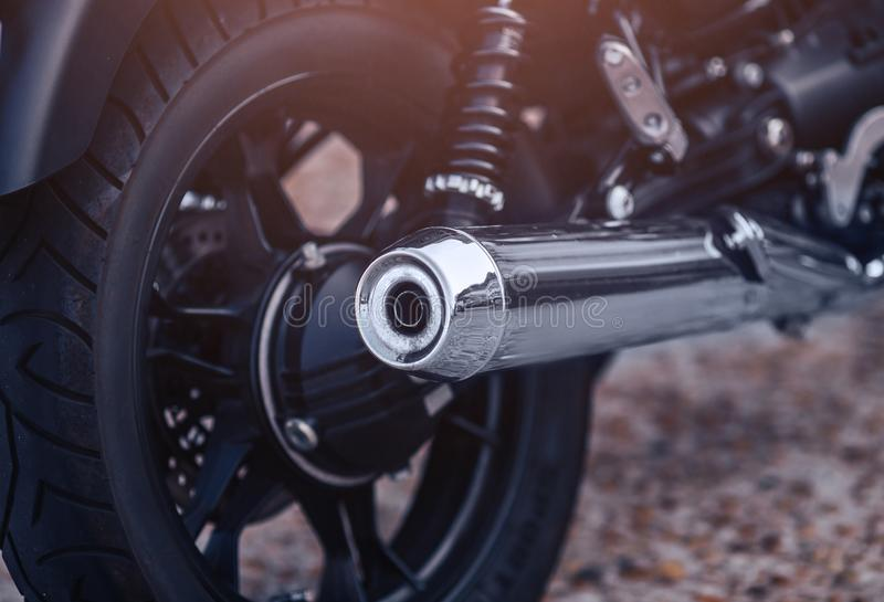 Close-up motorcycle exhaust pipe with classic wheel royalty free stock image